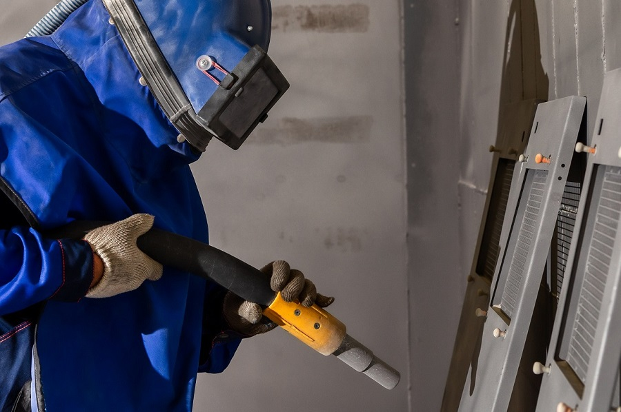 worker sandblasts components in preparation for powder coating